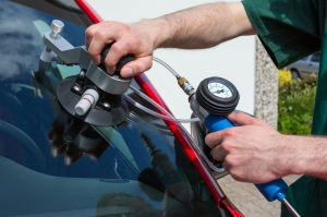 20443646 - glazier repairing windshield on a car after stone-chipping damage